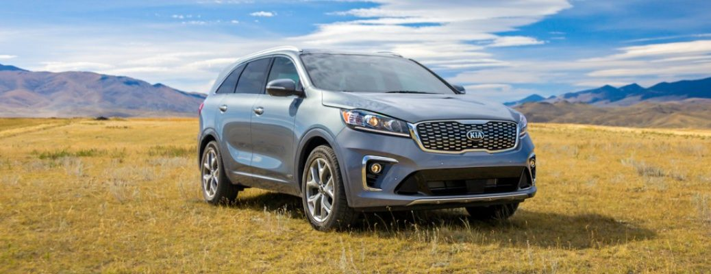2020 Kia Sorento exterior shot with gray silver paint color parked on a grass hill in the country with a blue and cloudy sky above