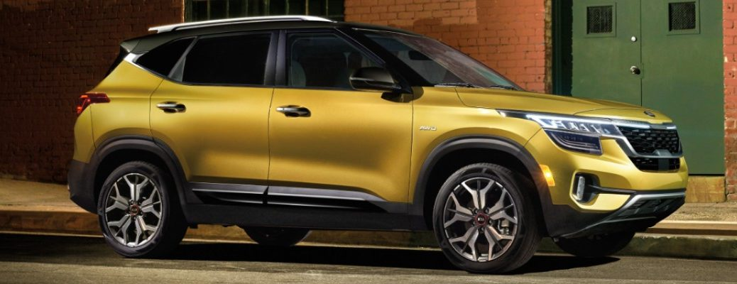 2021 Kia Seltos exterior side shot in Starbright Yellow with AWD badge parked beside a brick building