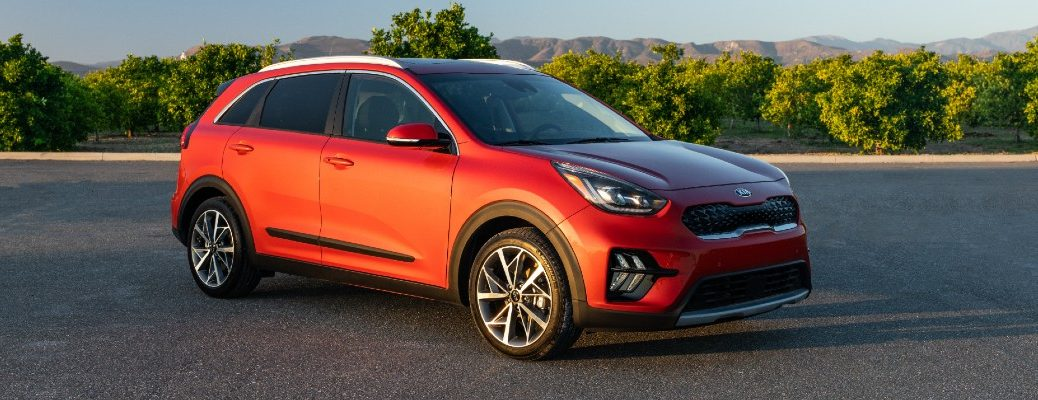 2020 Kia Niro Touring exterior shot with red paint color parked on a asphalt lot near a row of bushes