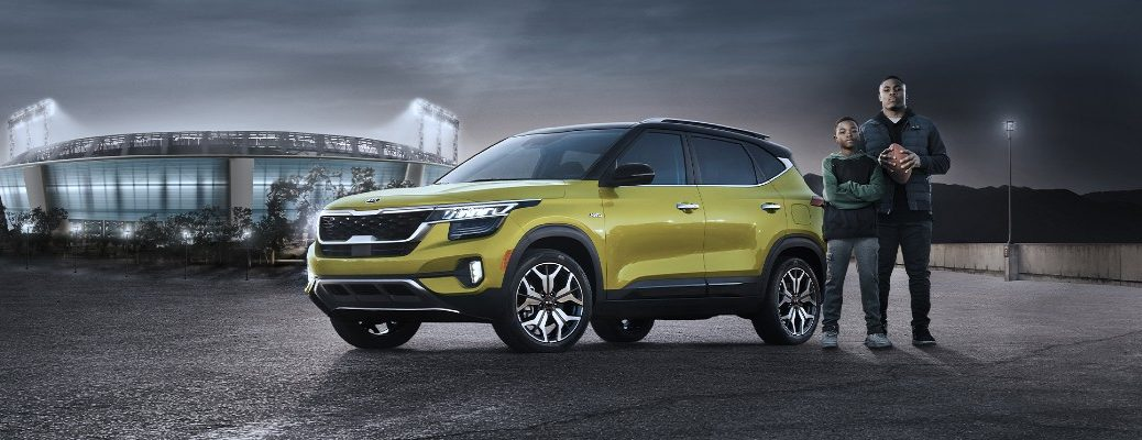 2021 Kia Seltos SUV model exterior shot with yellow paint color parked outside a football stadium with Raiders running back Josh Jacobs