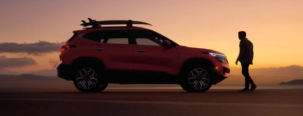 2021 Kia Seltos exterior side shot with red paint color parked on a sand dune as the sun sets