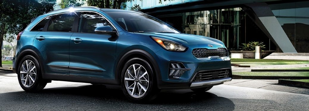 2020 Kia Niro exterior side shot with Deep Cerulean paint color parked in a plaza outside of a hotel lobby