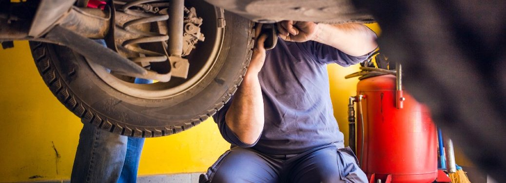 an auto mechanic in a blue jumpsuit fixing a tire on a lifted car in an auto service shop