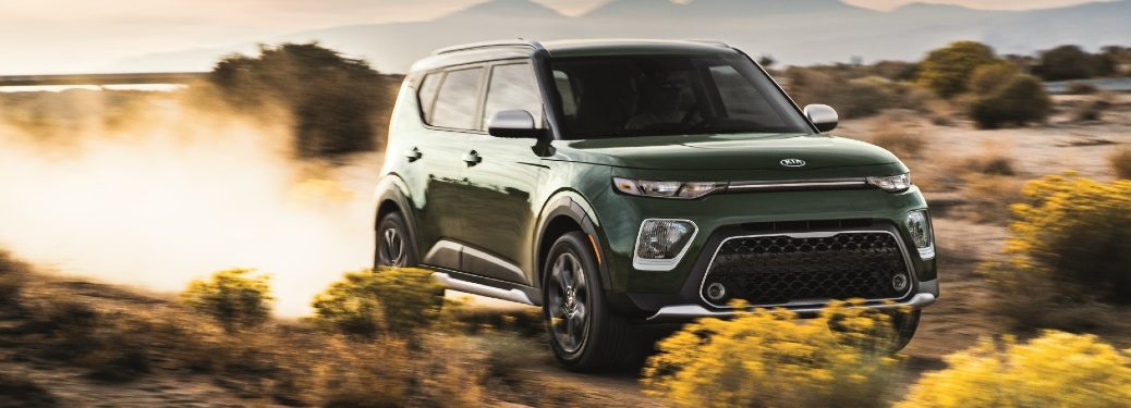 2020 Kia Soul X-Line exterior shot with Undercover Green paint color driving on a desert road as its back wheels kick up dust