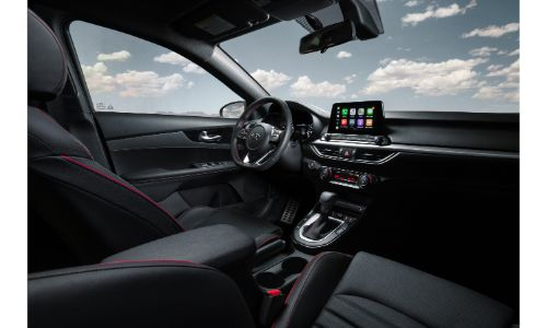 2020 Kia Forte interior shot of front seating upholstery with red stitching, steering wheel, and dashboard layout