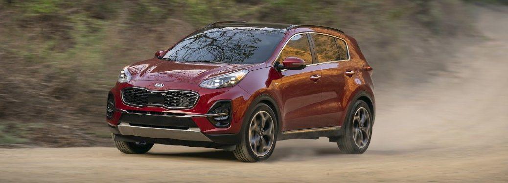 2021 Kia Sportage exterior shot with dark red paint color driving on a dirt gravel road and kicking up dust