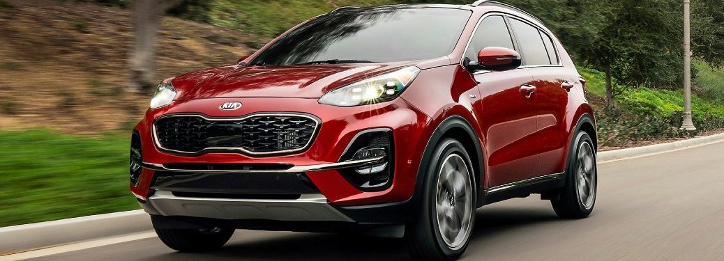 2021 Kia Sportage compact SUV exterior shot with Hyper Red paint color driving down a road