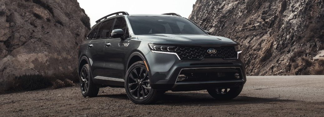 2021 Kia Sorento exterior shot with Gravity Gray paint color parked on a gravel plain surrounded by rocky cliffs