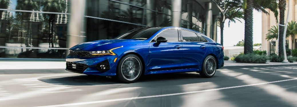 2021 Kia K5 GT exterior shot with blue paint color driving past a hotel surrounded by palm trees