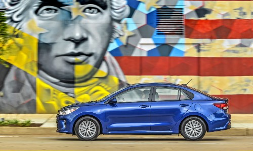 2020 Kia Rio exterior side shot with blue paint color parked next to American graffiti