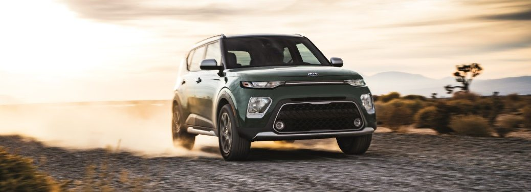 2021 Kia Soul X-Line exterior shot with green paint color driving on a dirt gravel road in the desert