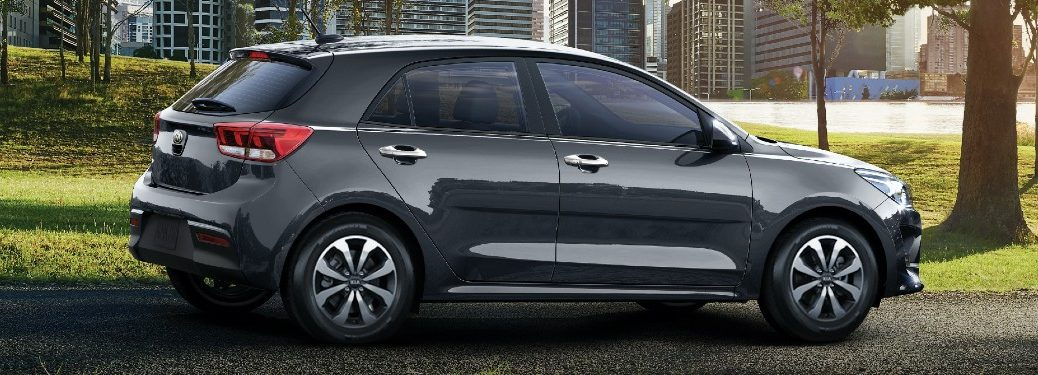 2021 Kia Rio 5-Door exterior side shot with Steel Gray paint color parked on a gravel path in a city park surrounded by trees