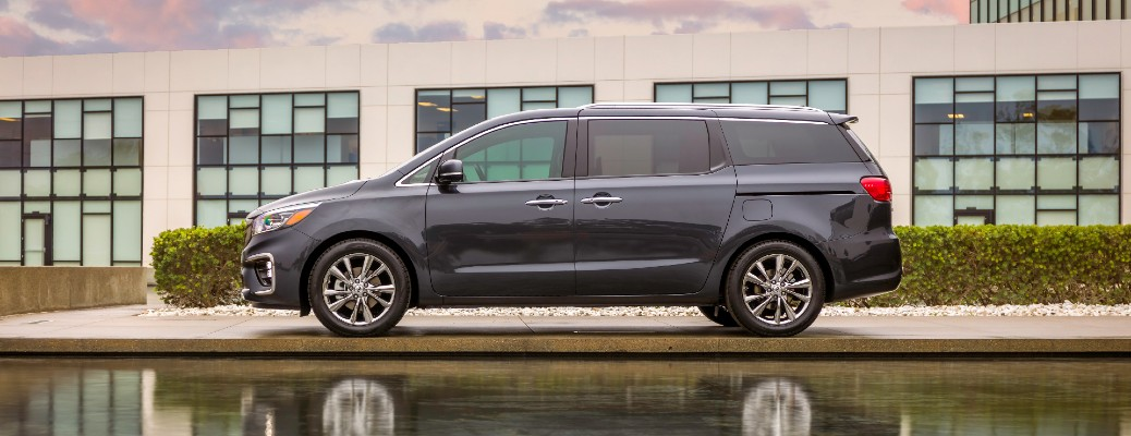 2021 Kia Sedona minivan exterior side shot parked outside of a building near a shallow pond