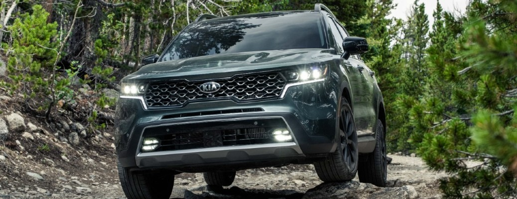 The front side of a green 2021 Kia Sorento driving off-road in a forested area.