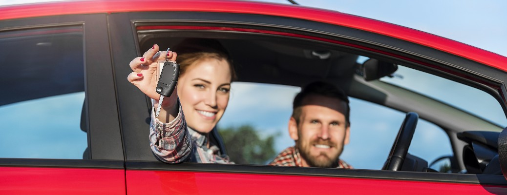 A younf couple in a red car smiling while holding a key.
