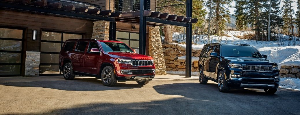 The 2022 Jeep Wagoneer and Grand Wagoneer parked by a cabin.