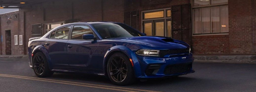 blue 2021 Dodge Charger front fascia passenger side driving on empty city road past brick building