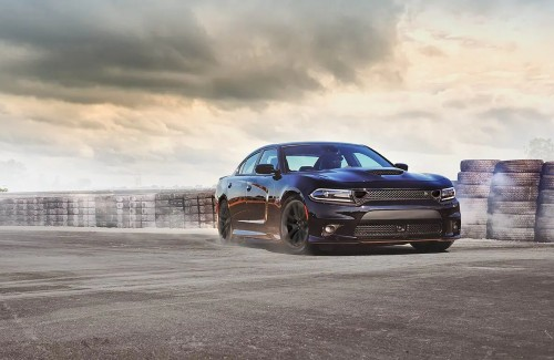 black 2021 Dodge Charger front fascia passenger side drifting on track surrounded by stacks of tires