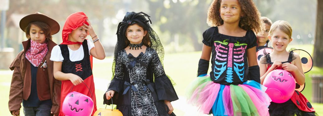 group-of-children-walking-down-sidewalk-in-Halloween-costumes
