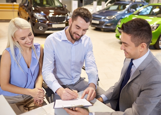 couple signing papers with salesman