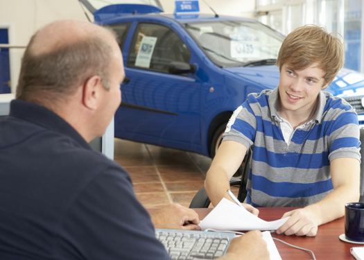 young man signing papers at a dealership