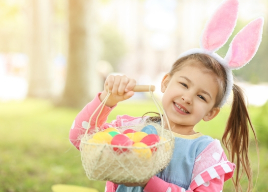 little girl with bunny ears on holding easter basket.