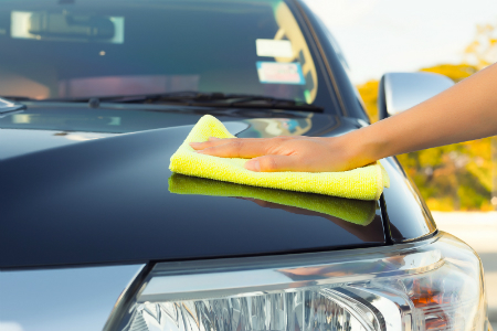 person drying car hood