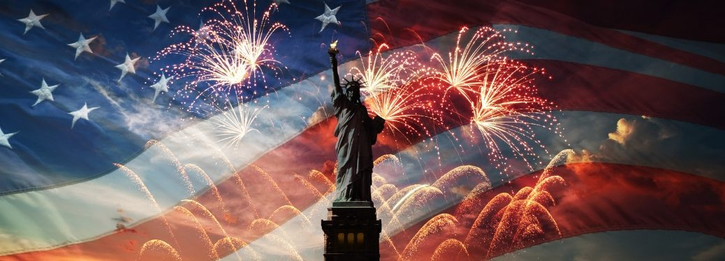 statute of liberty in front of flag and fireworks