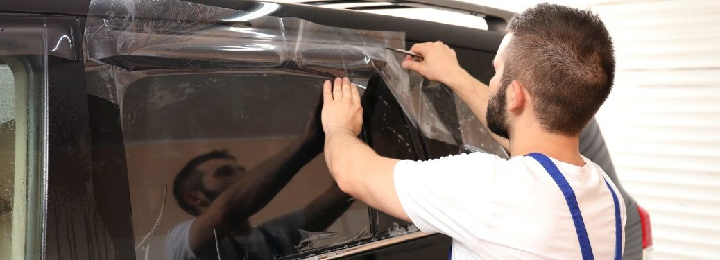 Worker removing tape off a vehicle after tinting the window