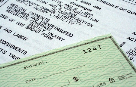 Close up of a check on top of an auto insurance bill