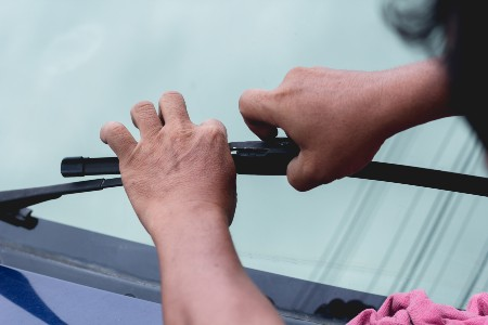 Close up of a person replacing a windshield wiper