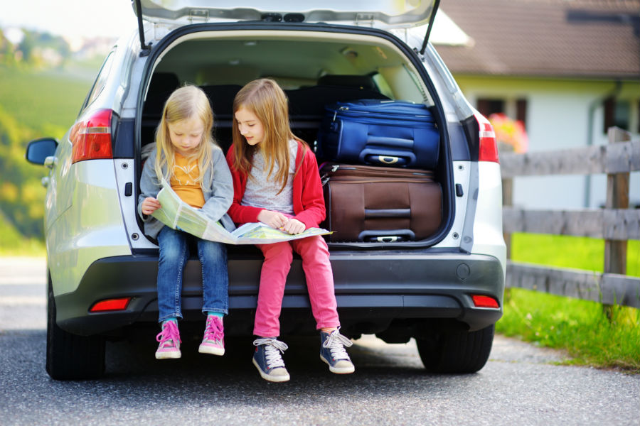 girls reading a map in the car
