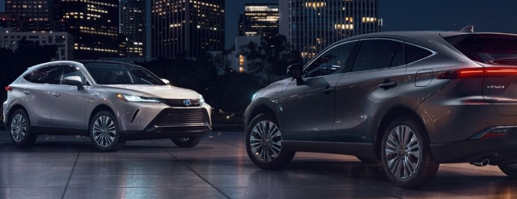 Two 2021 Toyota Venza parked facing each other before a row of well-lit buildings
