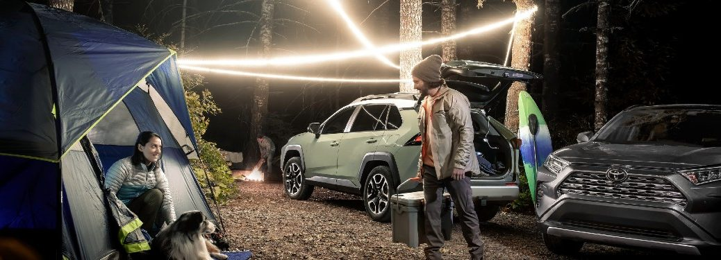 two 2021 Toyota RAV4 models parked in campsite in woods