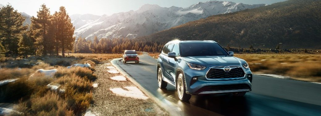 two 2021 Toyota Highlander models front fascia driving through forest and field