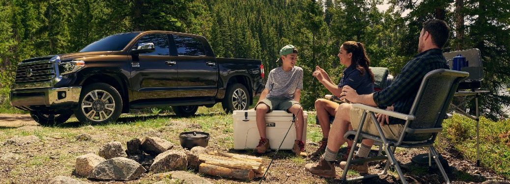 2021 Toyota Tundra parked in forest with family of three set up for camping