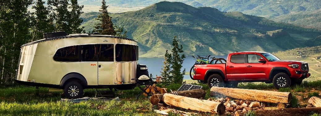 red 2021 Toyota Tacoma with camper attached parked in forest
