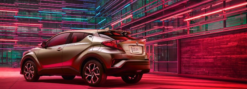 bronze 2021 Toyota C-HR rear fascia driver side parked next to building with red and blue lights