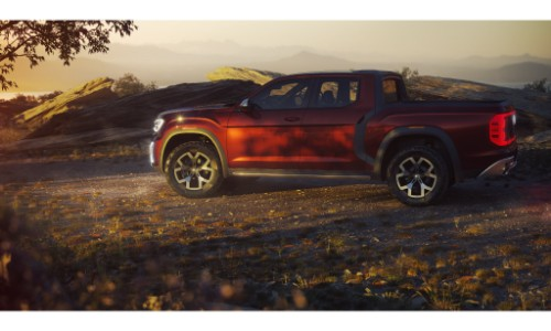 vw atlast tanoak concept pickup truck exterior side shot at sunset with shade from a nearby tree and rocky background