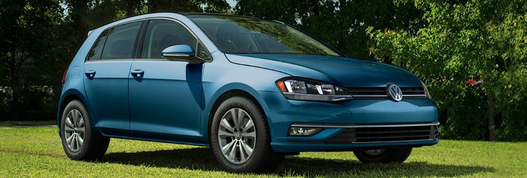 2018 Volkswagen Golf Teal parked in the shade and sun on green grass background