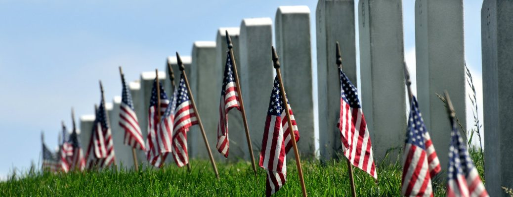 American flags planted in the grass ground next to a line of gravestones for soldiers on Memorial Day