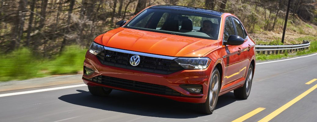 2019 Volkswagen Jetta R-Line exterior shot with orange paint color options driving near a country forest