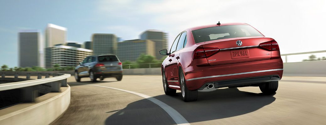 2019 Volkswagen Passat SE R-Line trim level exterior rear shot with Fortan Red Metallic paint color driving on a highway behind a Tiguan Limited
