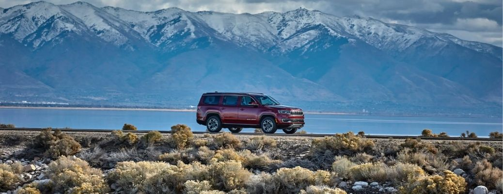 2022 Jeep Wagoneer in rugged land surrounded by water and mountains