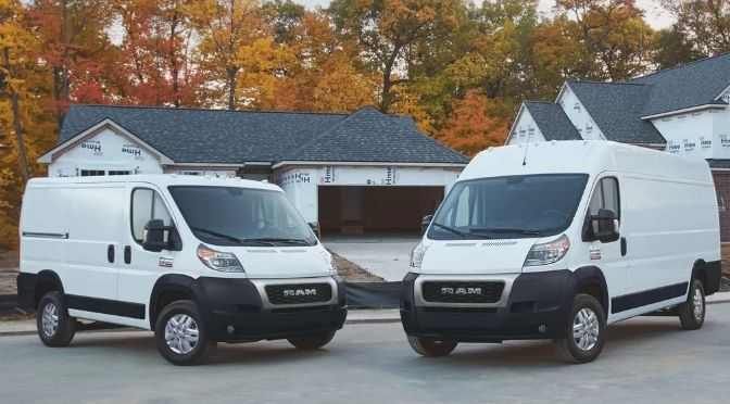 Two 2021 RAM ProMaster Cargo Vans parked next to each other outside a new house.