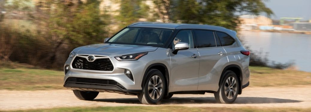 2021 Toyota Highlander driving on a muddy road front left-quarter view