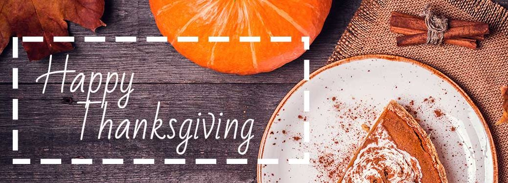 Happy Thanksgiving with pumpkin pie on a wood background
