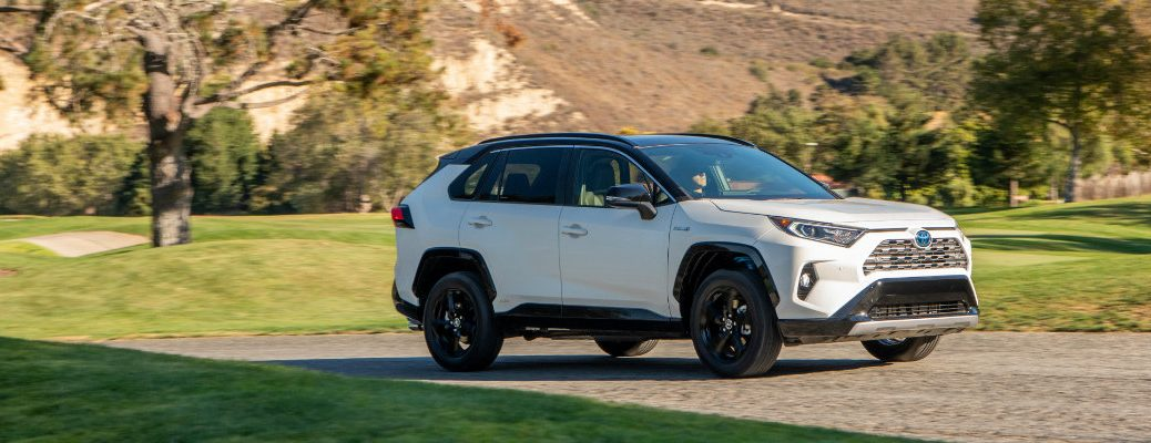 2019 Toyota RAV4 Hybrid XSE Trim exterior shot with white paint color parked in a field of grass next to small mountain hills