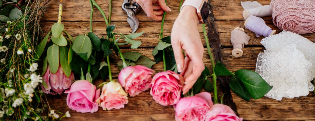 a florist cutting and arranging various flowers on a wooden table top for a Valentine's Day assortment