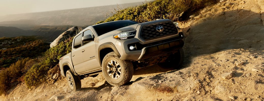 2020 Toyota Tacoma TRD off-road exterior shot with Cement paint color driving up a rocky hill